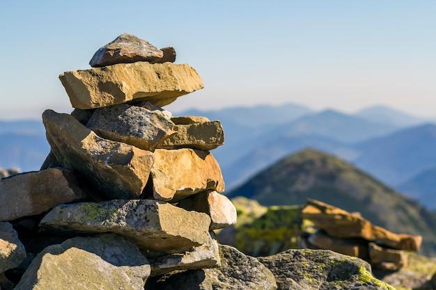 山のシーンで山の上に苔で覆われた石のスタック。バランスと調和の概念。禅の岩のスタック。野生の自然と地質の詳細。