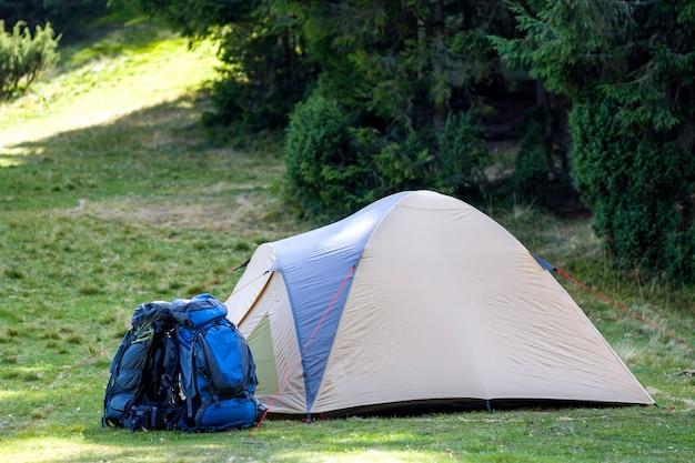 Туристический лагерь на зеленом лугу с свежей травой в лесу карпатских гор. туристическая палатка и рюкзаки в кемпинге. концепция активного образа жизни, активного отдыха, отдыха, спорта и отдыха.