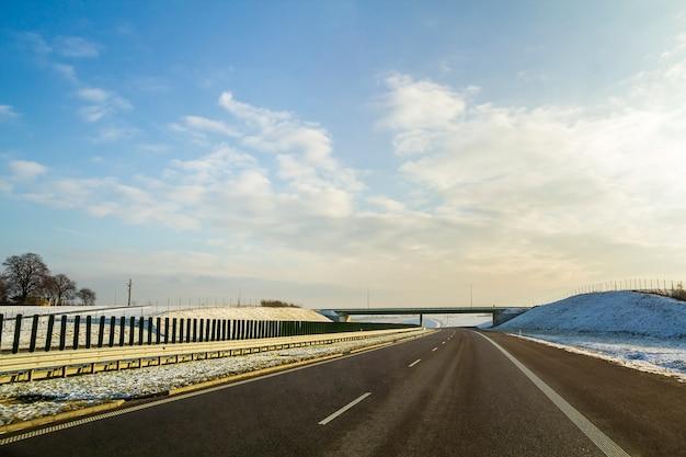 地平線へのアスファルト道路のある冬景色。
