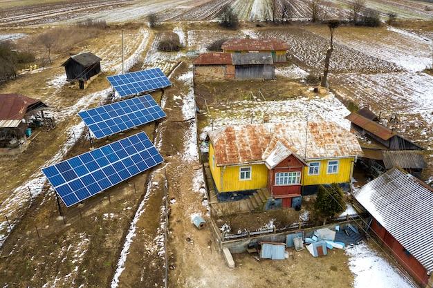 再生可能なクリーンエネルギーを生成するスタンドアロンの青い光沢のある太陽光発電パネルシステムの空中平面図。