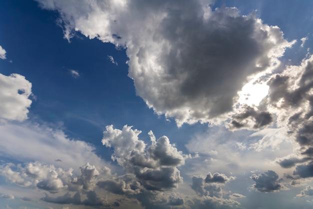 風とともに移動する深い青色の夏空に広がる太陽に照らされた明るい白いふくらんでいる雲の素晴らしいパノラマビュー。自然の美しさと力、気象学、気候変動の概念。