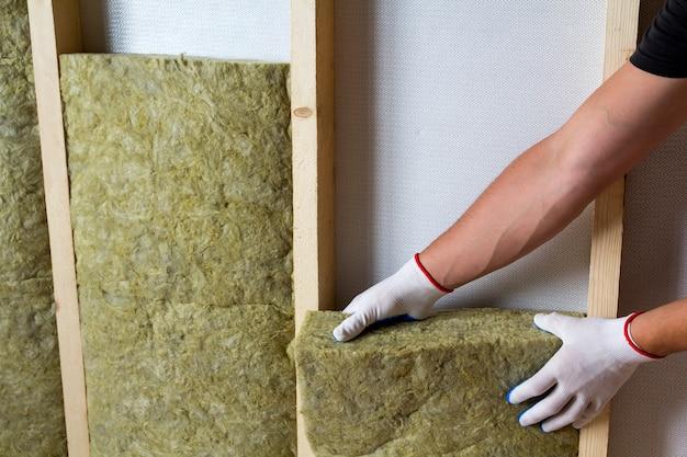 Конец-вверх рук работника в белых перчатках изолируя штат изоляции каменной ваты в деревянной рамке для будущих стен для холодного барьера. удобная теплая концепция дома, экономики, строительства и ремонта.