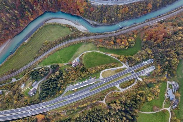 Верхний вид с воздуха рассвета скоростной дороги скоростного шоссе идя вне от подземного тоннеля между желтыми лесными деревьями осени и голубым рекой.