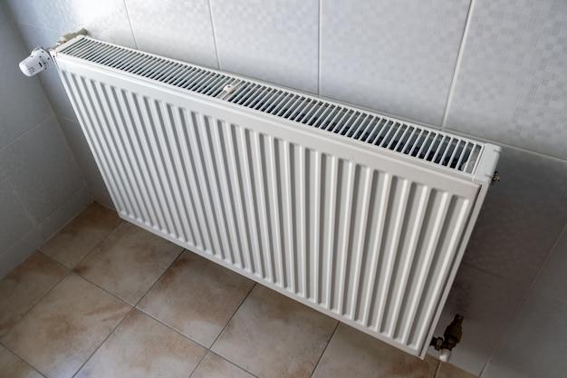 Радиатор отопления белого металла установленный на стене в интерьере комнаты.