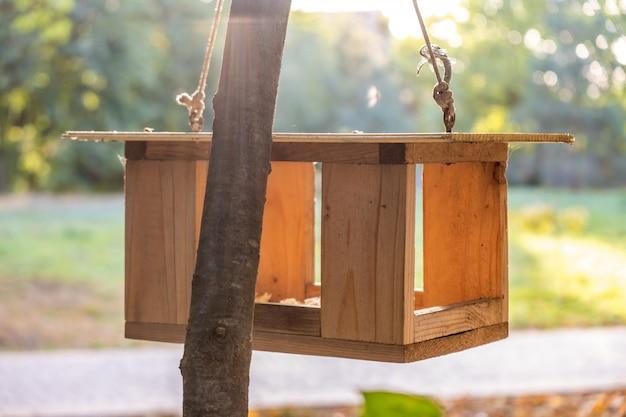 秋の公園の木に木製の鳥の餌箱。動物の野生動物のケアの概念。