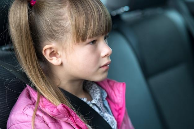 安全ベルトで固定されている後部座席の車に座っている小さな子供の女の子。