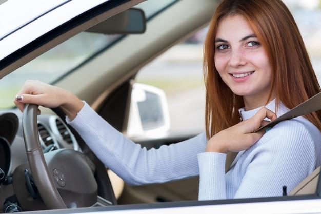 幸せな笑顔で車を運転するシートベルトで固定された若い赤毛の女性ドライバーの広角ビュー。