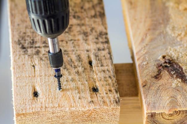 木の板にネジをねじ込む電動ドライバーで労働者の手