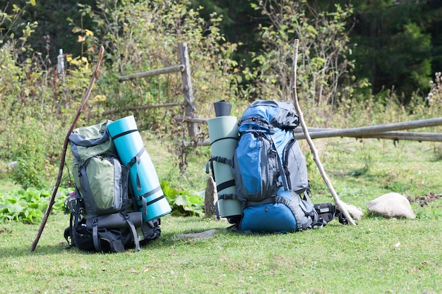 Два туристических рюкзака туристов, стоящих в горной долине в солнечный день