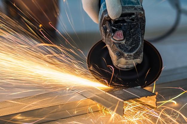 Конец-вверх инструментального металла работника с точильщиком.