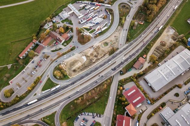 Сверху вниз вид с воздуха автострады межгосударственной дороги с движением автомобилей в сельской местности.