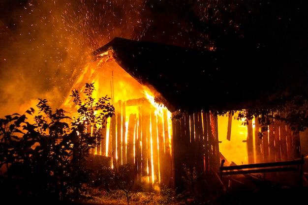 木造住宅または納屋は夜に火で燃えています。