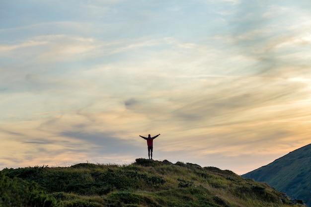 日没で山を登るハイカーの暗いシルエットは、勝者のように頂上に立っている彼の手を上げます。