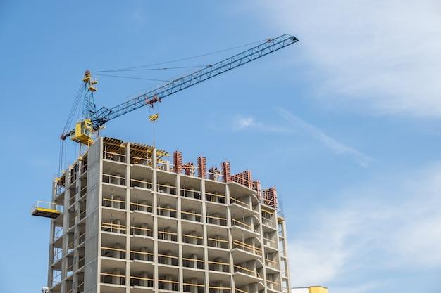 都市の建設中の高層マンションとタワークレーンのコンクリートフレーム。