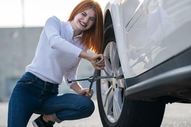 壊れた車のホイールを変更するレンチを持つ若い女性。