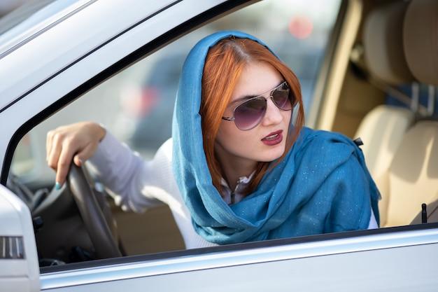 スカーフとサングラスが車を運転して若いおしゃれな女性ドライバー。