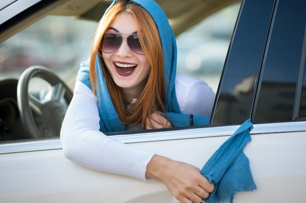 若いファッショナブルな女性ドライバーは、彼女のスカーフが車のドアに詰まっていて、それを引き出しています。