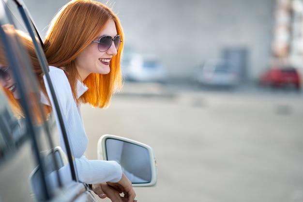 日当たりの良い夏の日に車のフロントウィンドウの外を見てサングラスの若いきれいな女性ドライバー。