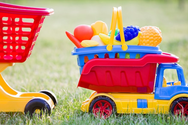 日当たりの良い夏の日に屋外で子供のための明るいプラスチック製のカラフルなおもちゃ。おもちゃの果物と野菜のバスケットを運ぶ車のトラックとショッピング手押し車。