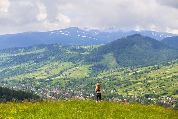 Вид сзади стройная молодая женщина, стоящая на травяной долине, зеленые горы в солнечный летний день
