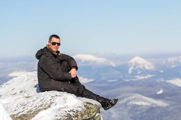 明るい晴れた冬の日に景色と達成を楽しんでいる雪に覆われた山の上に座っている一人の観光客のシルエット。アドベンチャー、アウトドアアクティビティ、健康的なライフスタイル。
