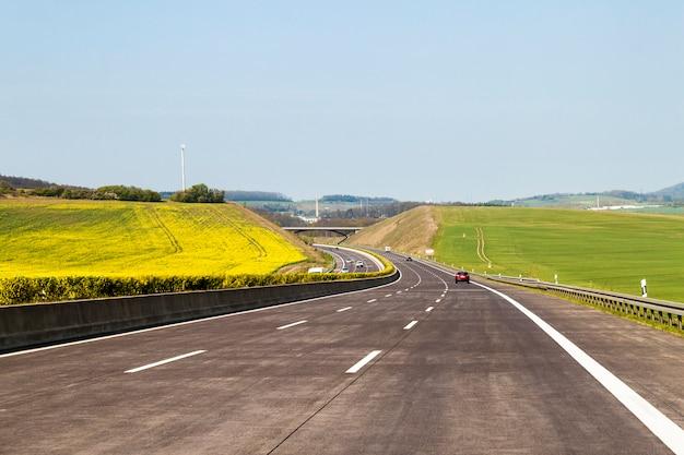 真新しい高速道路道路。夏の日の緑の野原の間の高速道路