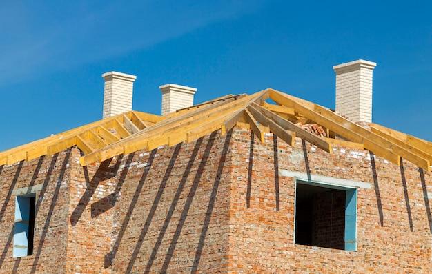 屋根工事。木製の屋根フレーム、白い煙突、黄色のレンガ造りの家の建設