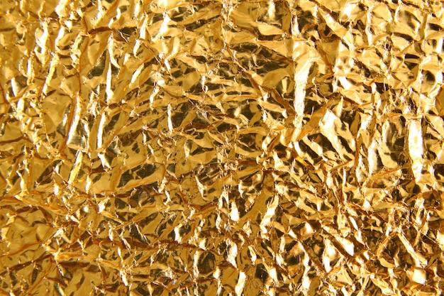 Предпосылка текстуры сияющего металла желтая золотая. металлический золотой узор
