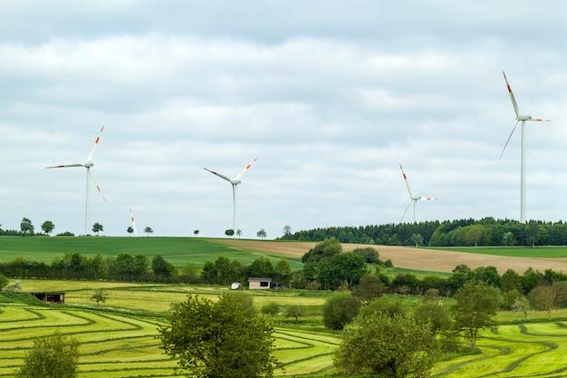 澄んだ青い空と手前のフィールドを持つ風力タービン再生可能エネルギー源の夏の風景