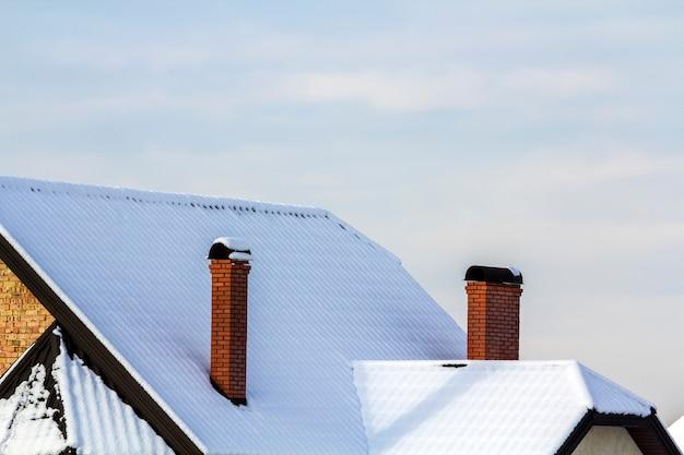 Крыша дома с кирпичными дымоходами, покрытыми снегом зимой