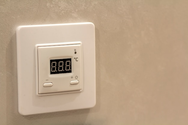 Белый электронный программируемый цифровой термостат на светлом фоне стены копирования пространства. климат-контроль, комфортная температура дома, концепция энергосбережения.