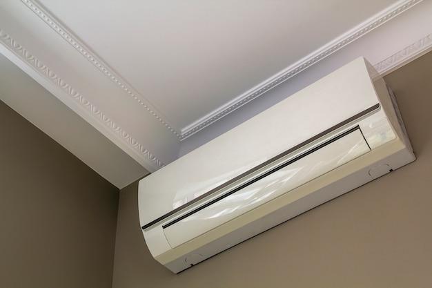 Прохладный кондиционер установлен в интерьере комнаты на белом потолке, а светлые стены копируют пространство. климат-контроль, удобная концепция дома.