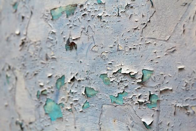 古いひびの入った抽象的なグランジビンテージテクスチャコピースペース背景、レトロなパターン。白い不規則な斑点は、明るい青のコンクリートまたは木製の壁または天井の平らな表面の剥離をペイントします。