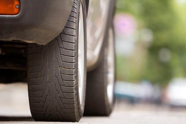 Деталь автомобиля, колеса с алюминиевыми дисками и новый черный резиновый протектор шин на свет размытой природы. транспортировка, безопасность, надежность, современная концепция дизайна.