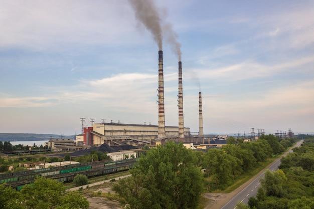 Вид с воздуха труб высокой дымовой трубы с серым дымом от электростанции угля. производство электроэнергии с использованием ископаемого топлива.