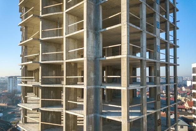 都市で建設中の背の高いマンションのコンクリートフレームの空撮。