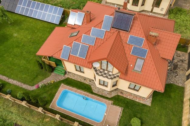 屋根の上にソーラーパネルと温水ラジエーターを備えた新しい自立住宅と、青いプールのある緑の庭の空撮。