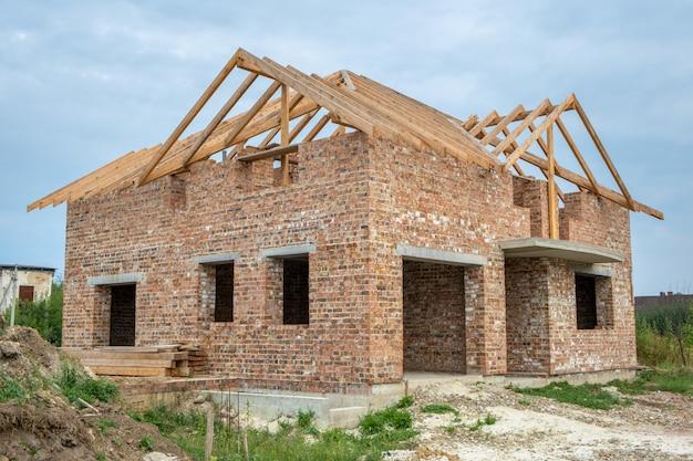 Строительная площадка с незаконченным кирпичным домом с деревянной кровельной рамой для будущей крыши под строительство.