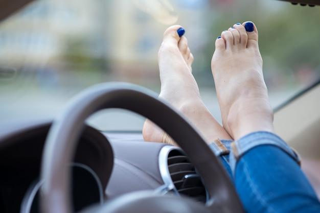 Закройте вверх ног водителя женщины отдыхая на приборной панели автомобиля.