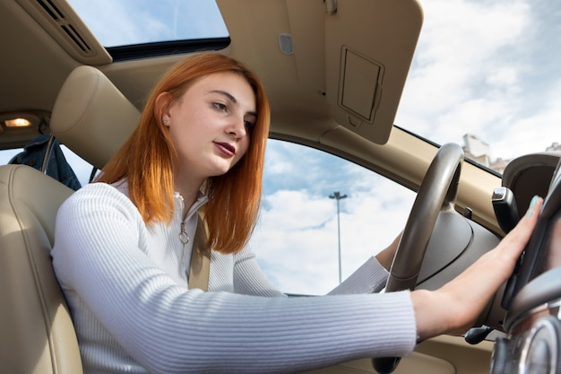 ヒーターを調整する車を運転するシートベルトで固定された若い赤毛の女性ドライバーの広角ビュー。