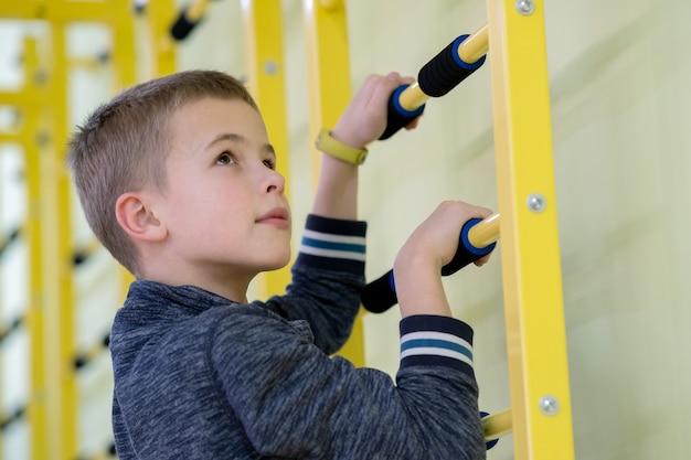 Мальчик маленького ребенка работая на баре лестницы стены внутри комнаты спортзала спорт в школе.