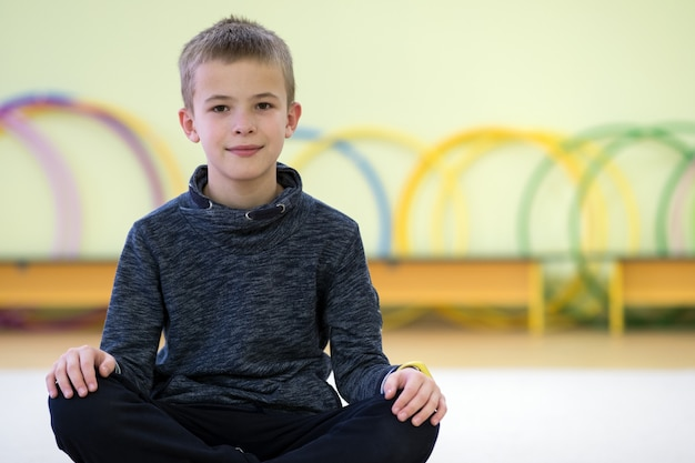 Мальчик маленького ребенка сидя и ослабляя на поле внутри комнаты спорт в школе после тренировки.