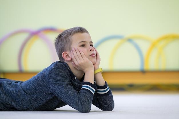 Мальчик маленького ребенка кладя вниз и ослабляя пока отдыхающ на поле внутри комнаты спорт в школе после тренировки.