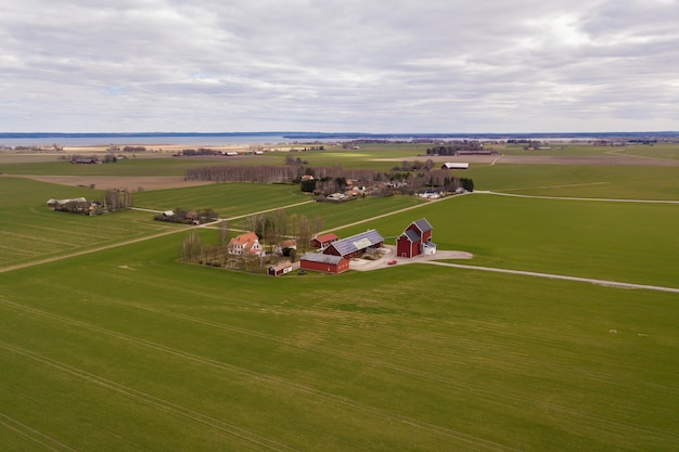 晴れた春の日に田園風景の平面図。木造建物、納屋、または家の屋根に太陽光発電パネルシステムを備えた農場。グリーンフィールドコピースペース。再生可能エネルギー生産。