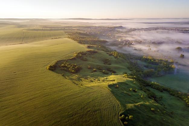 明るく青い空のコピースペースに緑の耕された丘、緑の木々、霧の谷の小さな家の平面図。夜明けの春の霧の風景パノラマ。