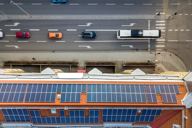 アパートの建物の屋根の太陽光発電パネルシステムの空撮。再生可能な生態学的なグリーンエネルギー生産の概念。