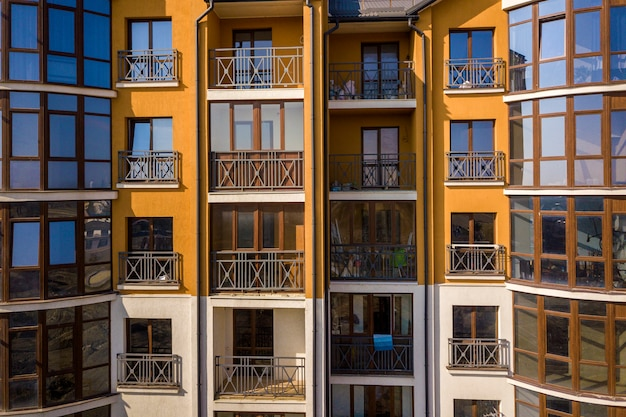 アパートまたはオフィスビルの詳細な外壁。鍛造バルコニーの手すり、光沢のある鏡の窓に映る青い空。建築の未来的なデザイン