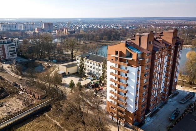 Вид с воздуха на новый высокий жилой дом в тихом районе на развивающийся городской пейзаж под ярким голубым небом.