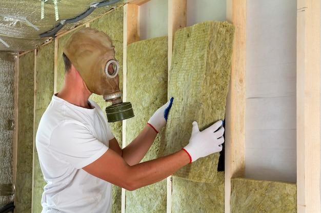 Молодой рабочий в противогазе, изолирующий минеральную вату, укомплектованный штатом в деревянной раме для будущих стен дома от холода и тепла. удобная теплая концепция дома, экономики, строительства и ремонта.