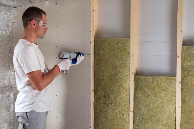 断熱材に取り組んでドライバーとゴーグルの労働者。壁梁の乾式壁、木枠のロックウールスタッフを絶縁します。快適で暖かい家、経済、建設、改修のコンセプト。